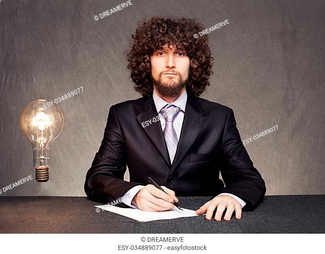 serious businessman is ready to write down the ideas while a glowing bulb standing in th air on grunge background