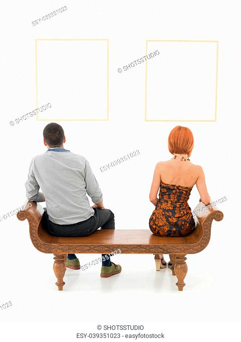 rear view of man an woman sitting on a wooden bench looking at empty frames displayed on a white wall in front of them