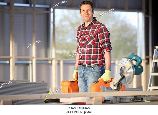 Carpenter workman carrying tools on indoor building construction site and smiling at camera