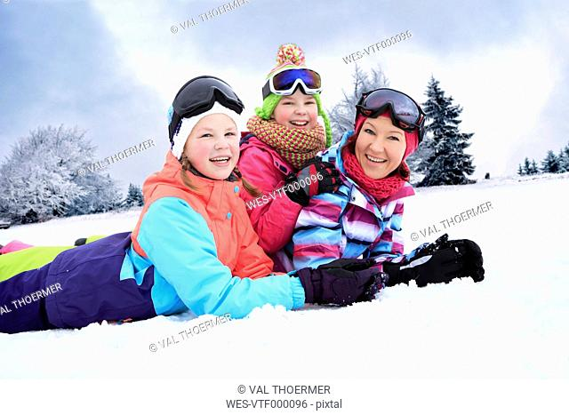 Germany, Masserberg, Mother and daughters lying in snow, smiling happily