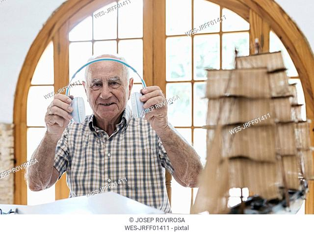 Portrait of confident senior man unpacking headphones from package with model ship on table