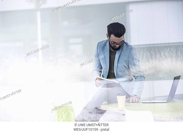 Young businessman sitting on desk, working