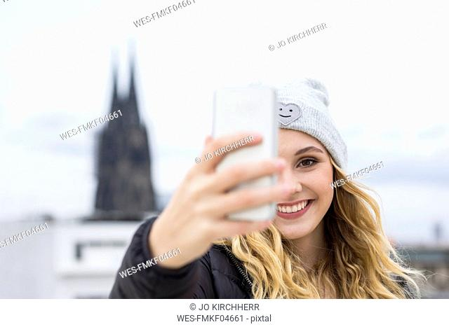 Germany, Cologne, portrait of laughing young woman taking selfie with smartphone