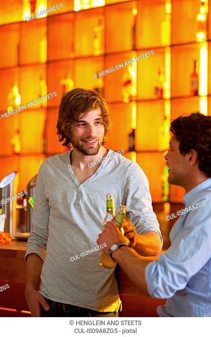 Two men standing at bar with bottles of beer