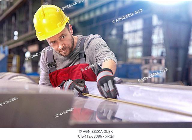 Focused male worker examining steel in factory