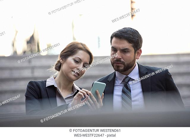 Businesswoman sharing cell phone with colleague