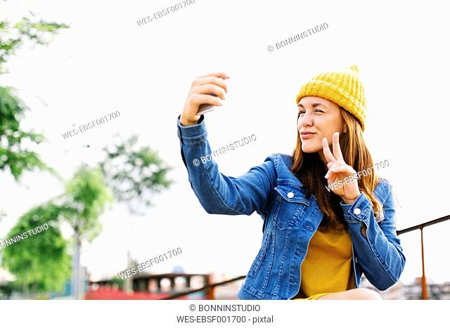 Smiling young woman showing victory sign while taking selfie