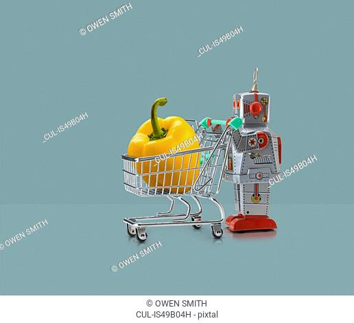 Toy robot pushing miniature shopping trolley with yellow pepper against blue background