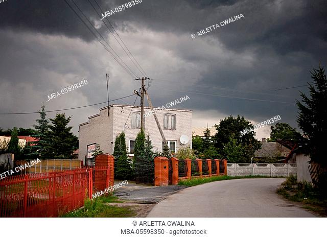 Gloomy stormy weather above brick house with antenna on roof in Odrzywol, Poland, Europe, Building, red bricks gate and fence