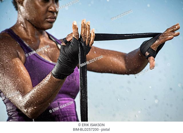 Black woman wrapping hands for boxing