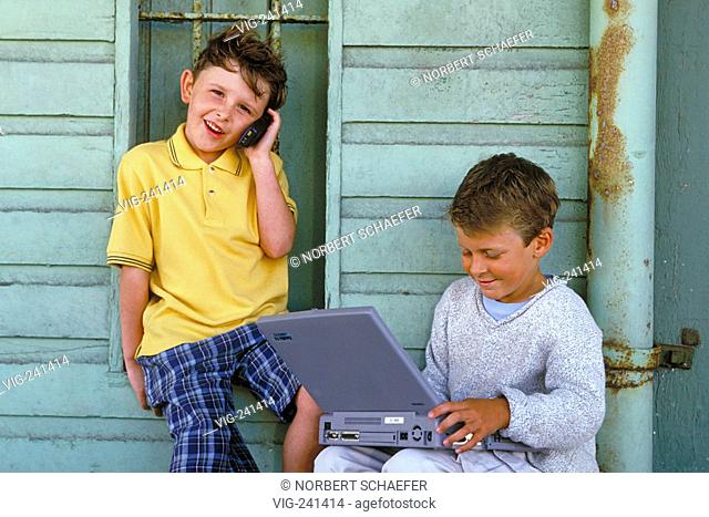 portrait, 2 boys in the age of 6-7 years are sitting with handy and laptop in front of a rotting greyblue painted wooden fassade  - GERMANY, 09/04/2004