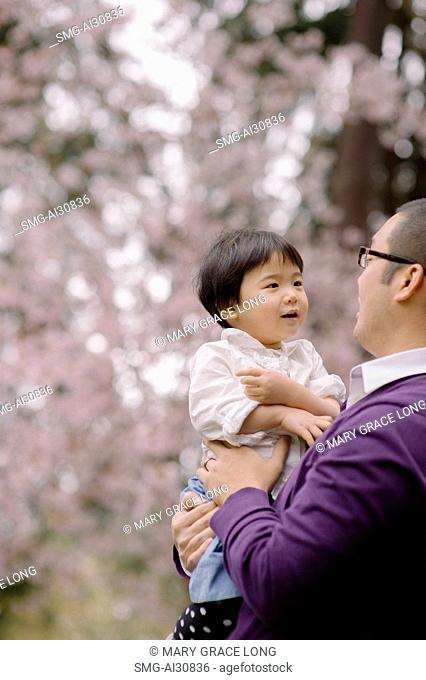 USA, Father face to face with daughter (2-3) in park