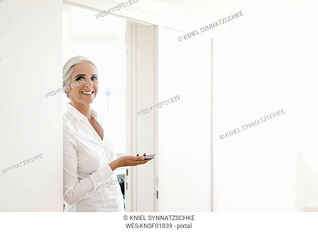 Portrait smiling businesswoman holding cell phone in office