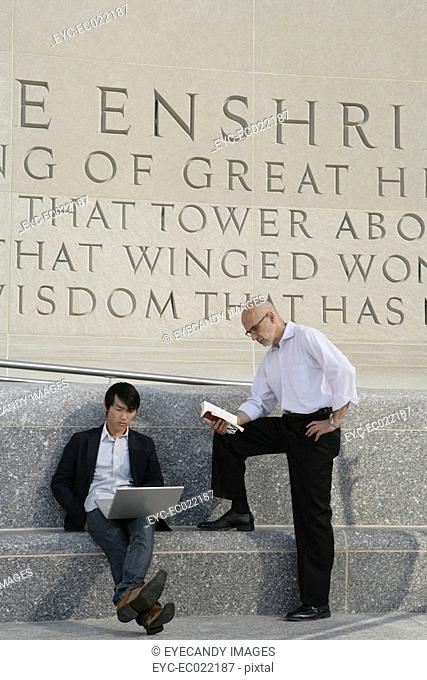 two men outside on laptop and reading a book
