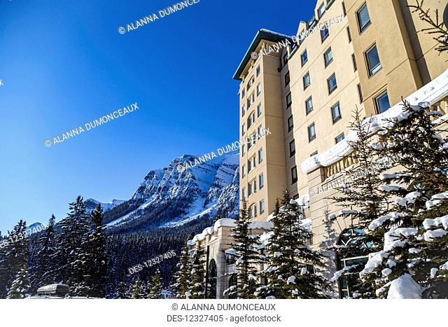 A Side Angle View Of The Winter Snow Covered Mountains And The Fairmont Chateau Lake Louise Resort Hotel In The Rocky Mountains; Lake Louise, Alberta, Canada