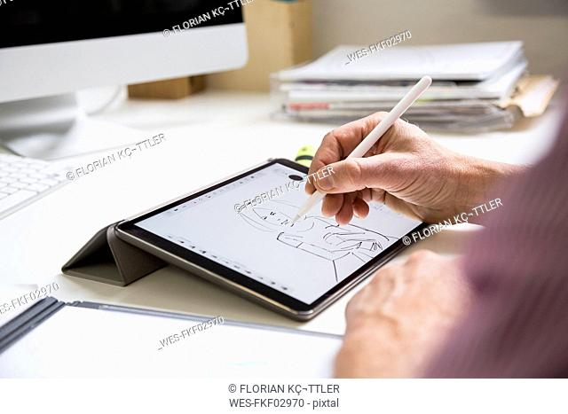 Close-up of man working at desk in office drawing female figure on tablet