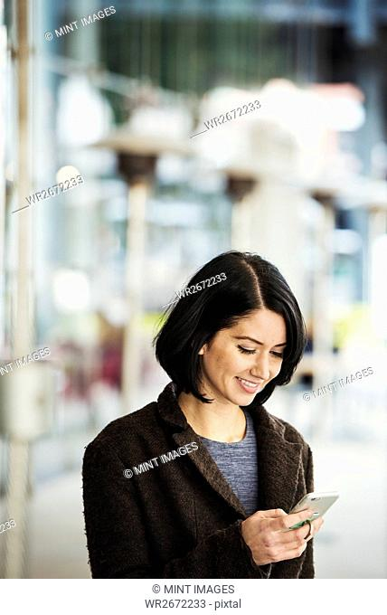A young woman holding at a cellphone and smiling