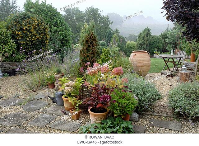 MIXED LATE SUMMER BORDERS WITH POTS ON PATIO IN COTTAGE STYLE GARDEN