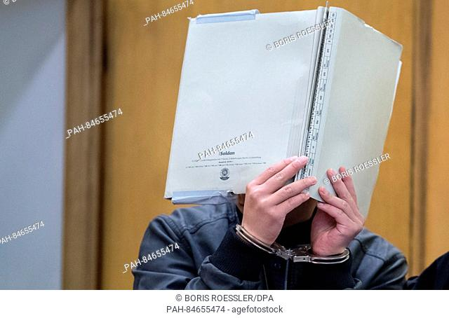 A defendant arrives in a courtroom while covering their face with a folder in Frankfurt am Main, Germany, 10 October 2016