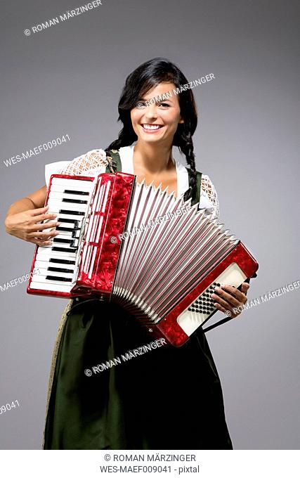 Portrait of smiling young woman with accordion wearing dirndl