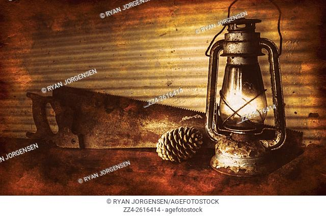 Vintage still life photo on a burning kerosene oil lantern lamp beside pinecone and rust antique saw in rustic country barn with aged wood floor