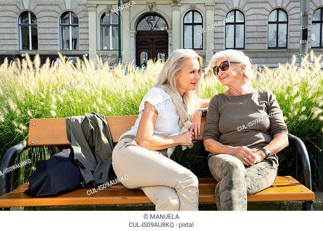 Mother and daughter sitting on bench together, outdoors