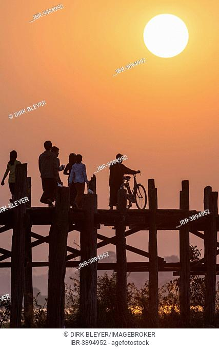 Locals and tourists walking on a teak bridge, U Bein Bridge across Thaungthaman Lake at sunset, Amarapura, Mandalay Division, Myanmar