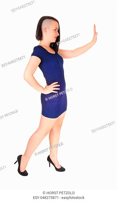 A gorgeous young woman in a tight blue dress standing in profile with.one hand raised, gesturing NO, isolated for white background
