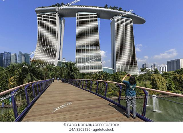 Young woman taking a picture of the Marina Bay Sands hotel from the gardens by the bay