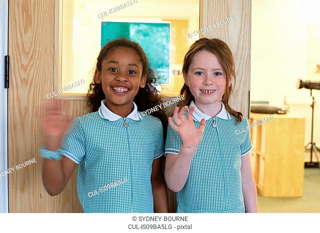 Portrait of two schoolgirls waving in primary school