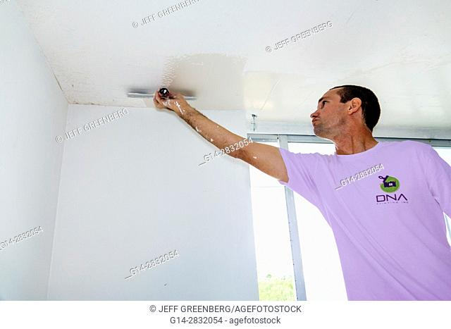 Florida, Miami Beach, home improvement, remodeling, contractor, plastering, ceiling, Hispanic, man, worker, tool, trowel, reaching
