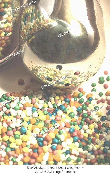 Faded retro macro photograph on an ingredient shaker pouring a sprinkle of 100s and 1000s