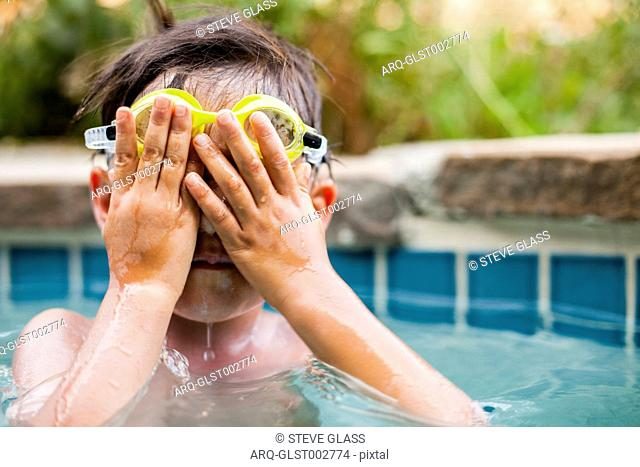 A Boy Swimming In A Pool And Covers His Face And Goggles With His Hands