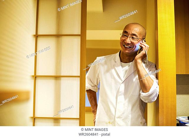 A chef in a small commercial kitchen, an itamae or master chef on his smart phone