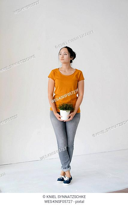 Young woman standing at a wall holding potted plant