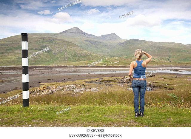 Young Woman looking toward Mountain on Isle of Mull, Scotland, UK