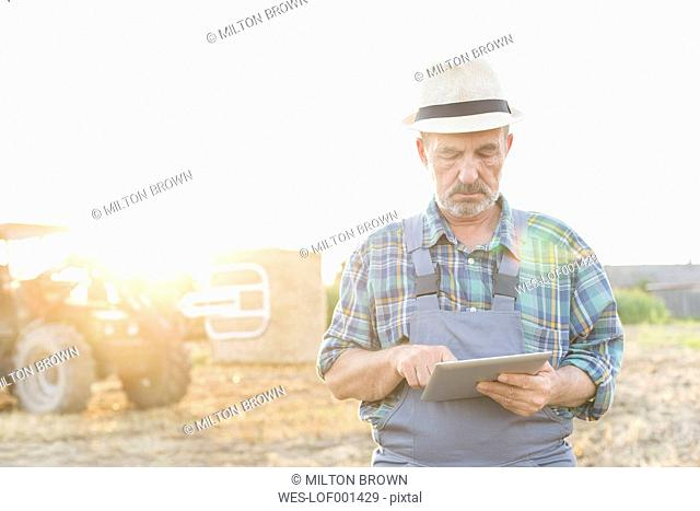 Farmer with digital tablet on field