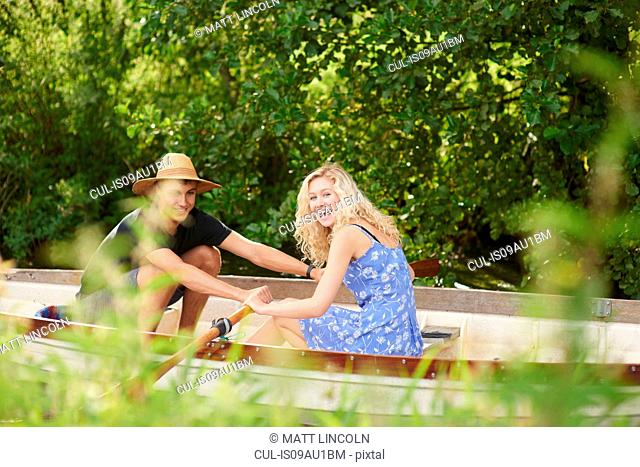 Portrait of young couple rowing river rowing boat