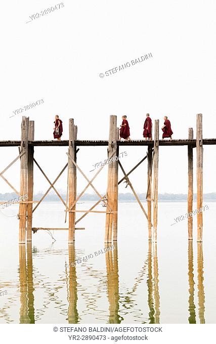 Monks crossing U Bein bridge, Amarapura's Taungmyo lake, Mandalay region, Myanmar