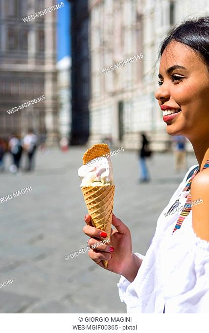 Italy, Florence, Piazza del Duomo, happy young woman holding ice cream cone