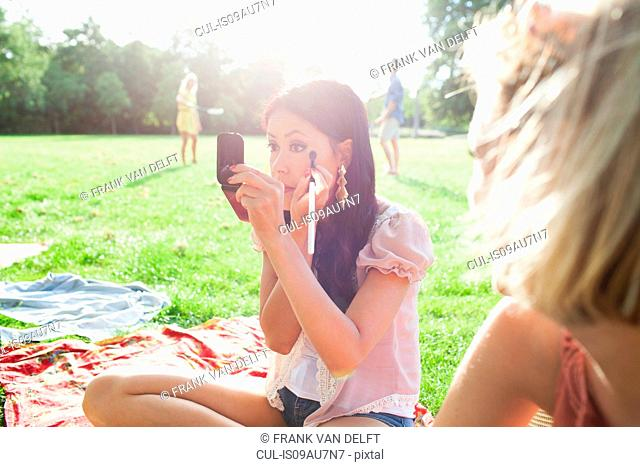 Female friends applying make up at park party