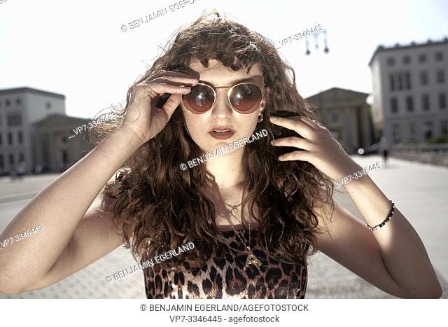 young woman touching sunglasses, in Berlin, Germany