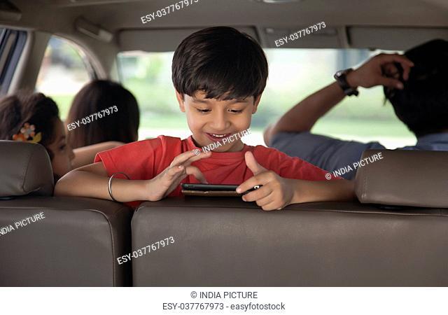 Portrait of happy boy using digital tablet in back seat of car