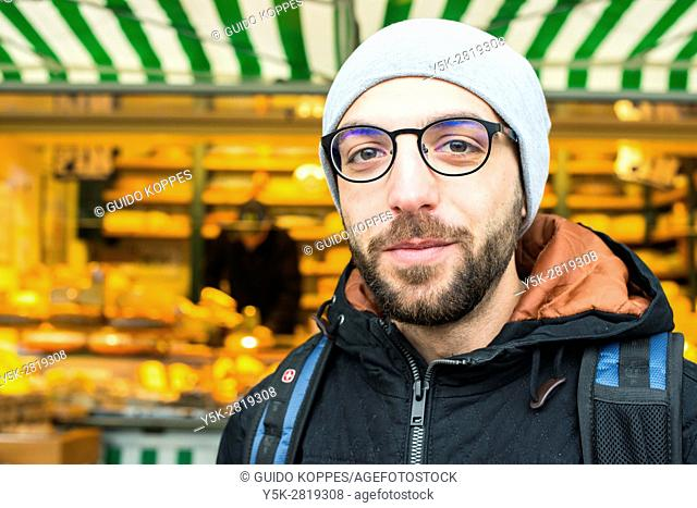 Tilburg, Netherlands. Former Syrian refugee visiting a Dutch market cheese stall at the weekly saturday market as part of his integration process