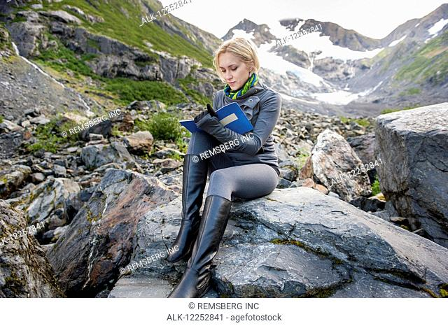 Woman sitting on a boulder and writing in her journal, Portage Valley, Southcentral Alaska