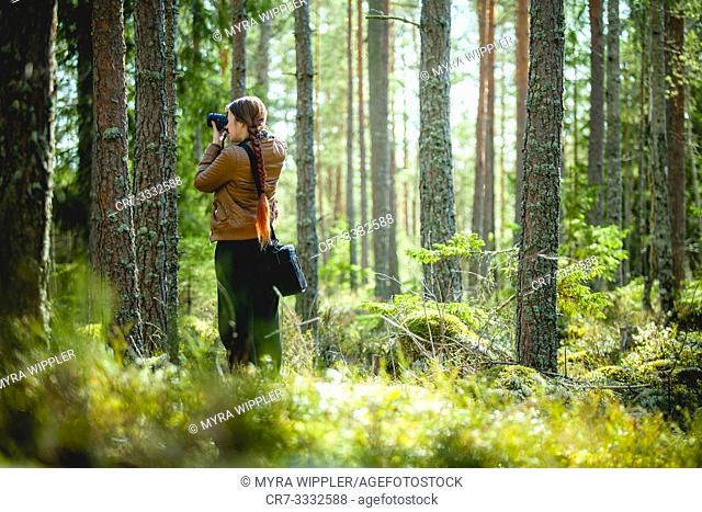 Girl photographing in a forest in Östergötland, Sweden