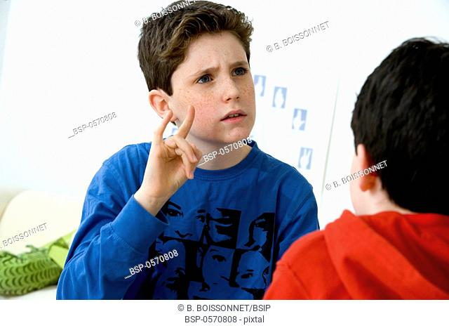 SIGN LANGUAGE Models. Do not use for HIV. A young boy using the French sign language to discuss with his hearing-impaired brother