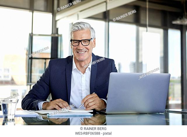 Businessman working at laptop, taking notes in notebook