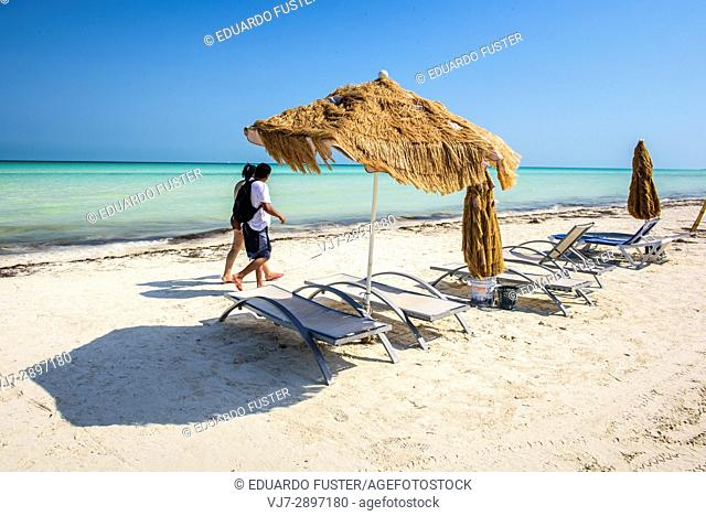 Couple walking and chaise-longue. in a beach in Isla Holbox, Quintana Roo (Mexico)
