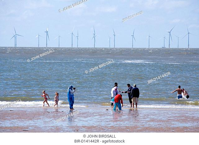 People on New Brighton beach Liverpool Bay, with the Burbo Bank offshore wind farm which comprises 25 wind turbines in the background